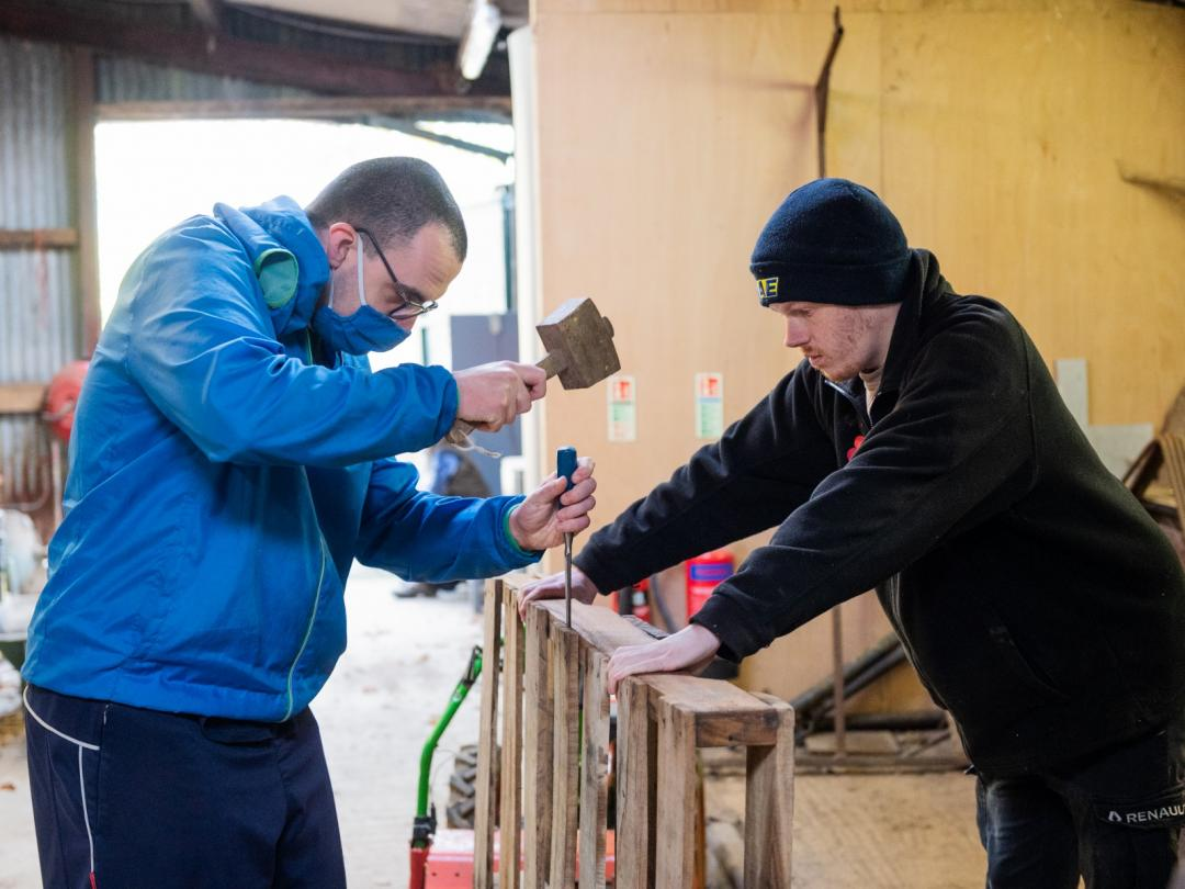 Co farmers Jamie, left, and volunteer Will ,right, help break down pallets at Blenheim Estate's workshop